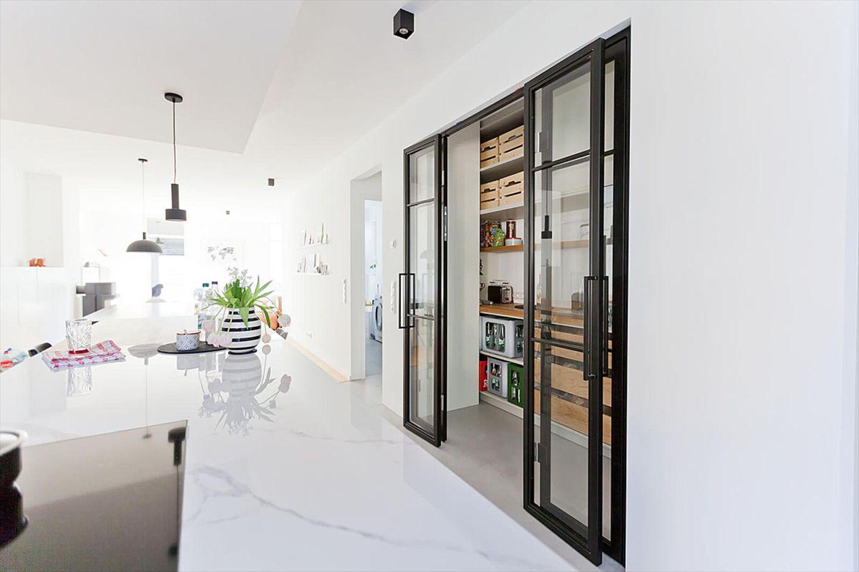 Lofttür mit Schiebefunktion vor einer Küchennische.