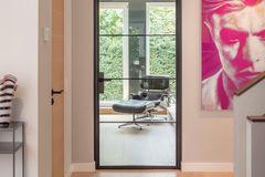 Lofttür aus Glas und Stahl von Stolwarker zwischen einem Flur und einem Wohnzimmer..