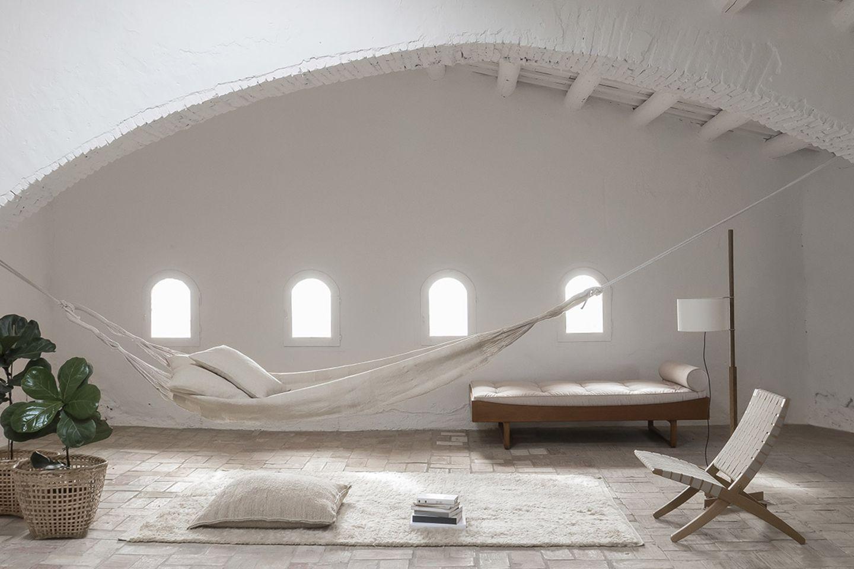 """Komplett weiß gestrichener Raum mit südländischem Flair und Textilien aus der """"Wellbeing""""-Kollektion von Nanimarquina"""
