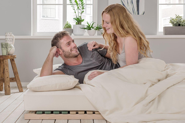 """Pärchen, das auf einer Matratze mit Lattenrost und in der Bettwäsche """"Kastilia"""" von Allnatura liegt"""