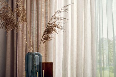Zwei unterschiedlich große Vasen mit getrockneten Gräsern vor unifarbenen Gardinen aus recyceltem Polyester von Saum und Viebahn