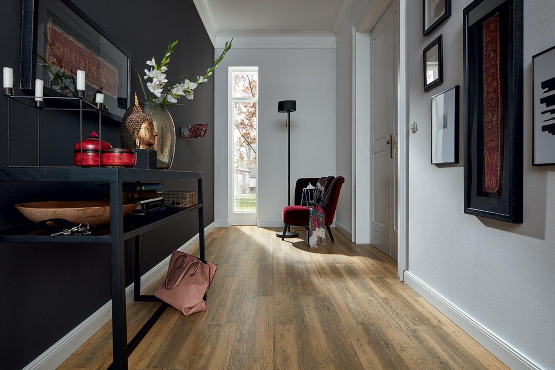 Stilvoll und hochwertig eingerichteter, länglicher Flur mit einem Designboden in Holzoptik von Jab Anstoetz