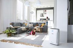 """Luftreiniger """"AC2889"""" von Philips in einem Wohnzimmer mit einem jungen Mädchen auf einem Teppich und der Mutter im Hintergrund"""