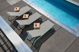 Drei nebeneinanderstehende Sonnenliegen mit eingehängtem Tablett an einem Pool