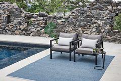 """Outdoor-Teppich """"Mono"""" von Pappelina in Ozeanblau vor einer Steinmauer an einem Pool"""