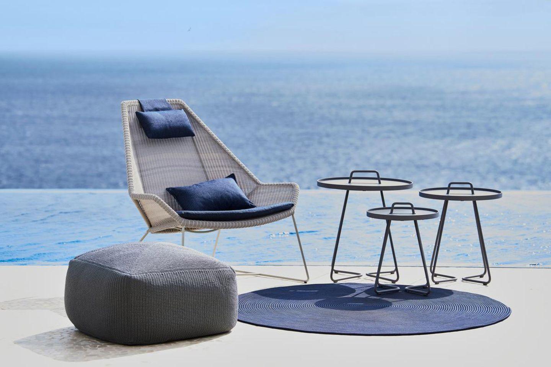 """Stilvolle Outdoor-Sitzecke mit dem Teppich """"Infinity"""" von Cane-line in Blau und mit Blick aufs Meer"""