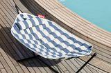 Hängematte von Fatboy mit blauen Streifen auf einem Holzdeck am Pool.