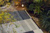 """Riesiger Outdoorteppich """"Tres Salvia"""" in einem opulenten, grün bepflanzten Innenhof"""