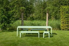 Bänke, Hocker und ein großer Tisch im Garten vor einem kleinen Waldstückchen