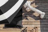 """Sitzbank """"Attackle"""" von Fatboy, die aussieht wie eine Ballonfigur in Dackelform, neben einem schwarzen Sitzsack und einem Sonne…"""