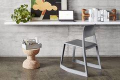 """Hocker """"Cork"""" als Ablagefläche vor einem Wandschreibtisch mit Laptop, Büchern, Pflanzen und einem Bild"""
