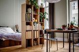 Bücherregal aus Wellpappe als Raumteiler zwischen Bett und Esstisch