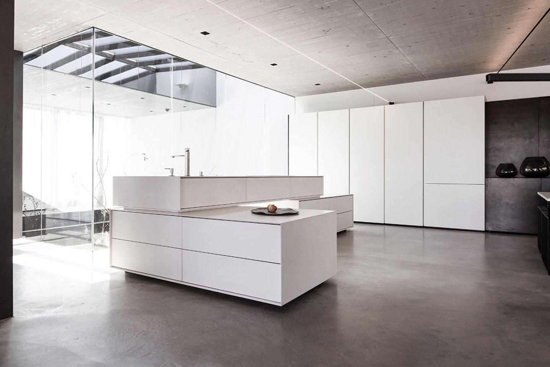 Weiße, skulpturale Blockinsel von Steininger in einem Loft mit großer Fensterfront