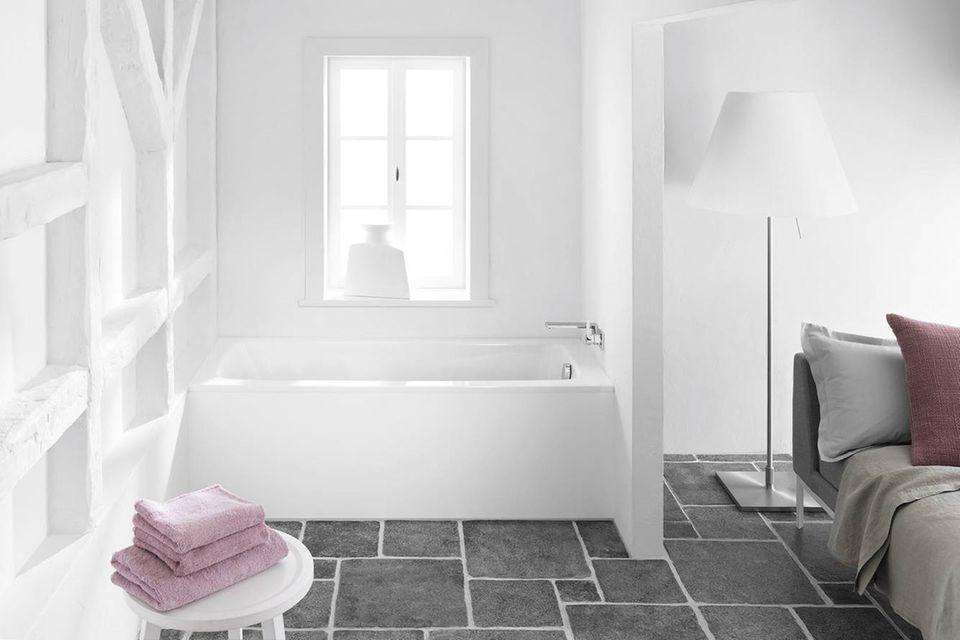 """Schlafzimmer mit weißer Badeecke – inkl. der Badewanne """"Cayone"""" von Kaldewei."""