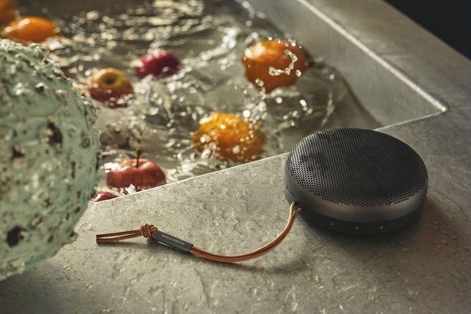 """Gefülltes Wasserbecken mit Obst drinnen, daneben: der mit Wasser bespritzte Bluetooth-Lautsprecher """"Beosound A1"""" von Bang&Olufs…"""