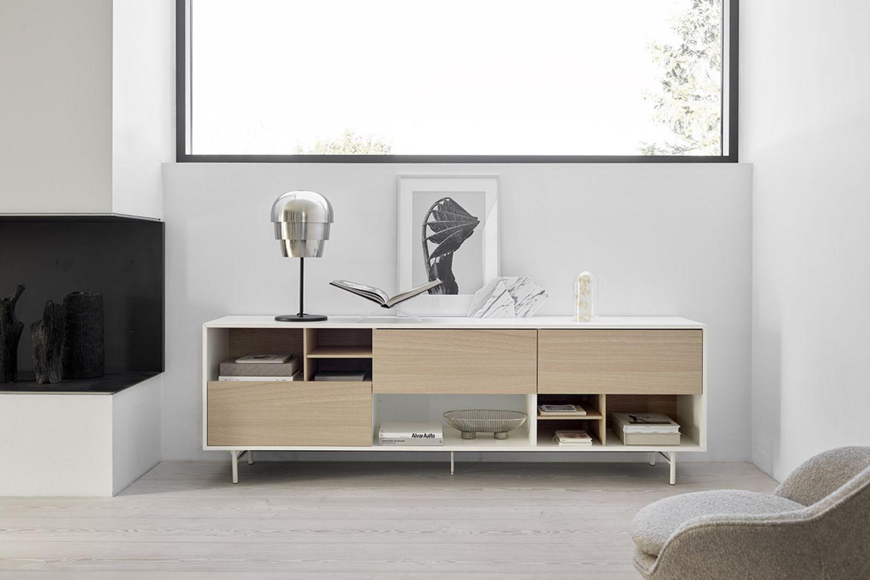 """Dekoriertes Sideboard """"Manhattan"""" von BoConcept in einem hell und modern eingerichtetem Raum inklusive Kamin mit dunkler Glasfr…"""