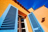 Orangefarbene Hausfassade mit hellblauen Fensterläden