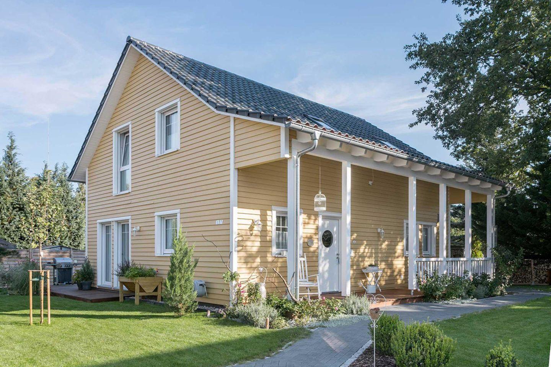 Idyllisches Schwedenhaus von Schwörer mit Vorgarten und einer Fassade in Goldocker