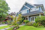 Großes Haus mit blauer Fassade und Vorgarten in einem Vorort von Amerika