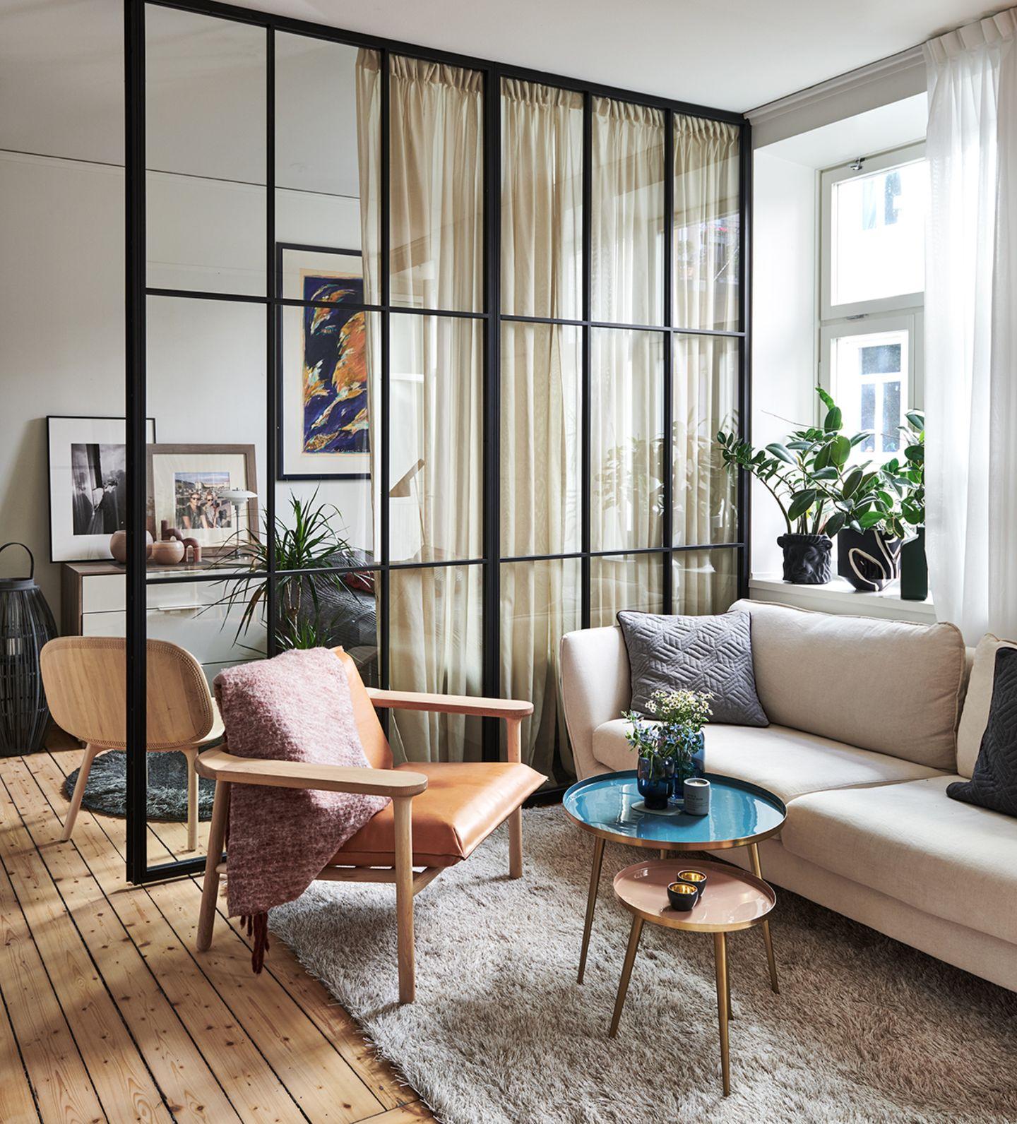 Raumtrenner aus Glas und Stahl, Im Vordergrund ein kleines Wohnzimmer