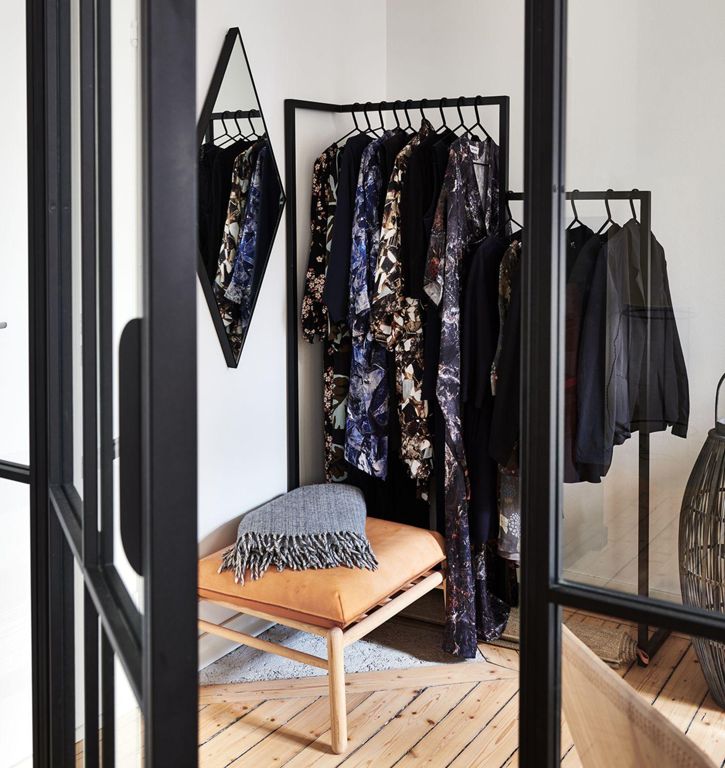 Blick durch eine Glasstahltür auf eine Ankleide mit Kleiderständern.
