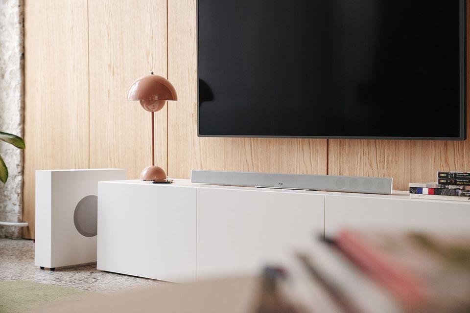 """""""Cinebar 11"""" in Weiß von Teufel unter einem großen, an der Wand angebrachten Flachbildfernseher"""