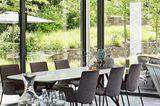 Hohe Wohnzimmerfenster machen es möglich: Drinnen essen und trotzdem das Grüne genießen
