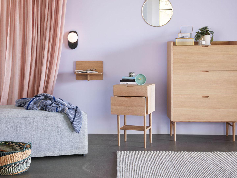 Schlafzimmer mit Wandfarbe in Flieder und hellem Holz