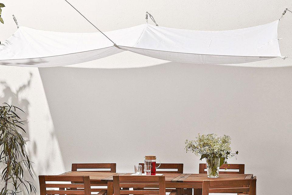 """Sonnensegel """"Dyning"""" von Ikea über einen Gartentisch und Gartenstühle aus Holz gespannt"""