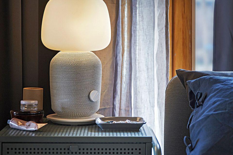 """Tischleuchte """"Symfonisk"""" von Ikea mit WiFi auf einem Nachttisch neben einem Bett"""