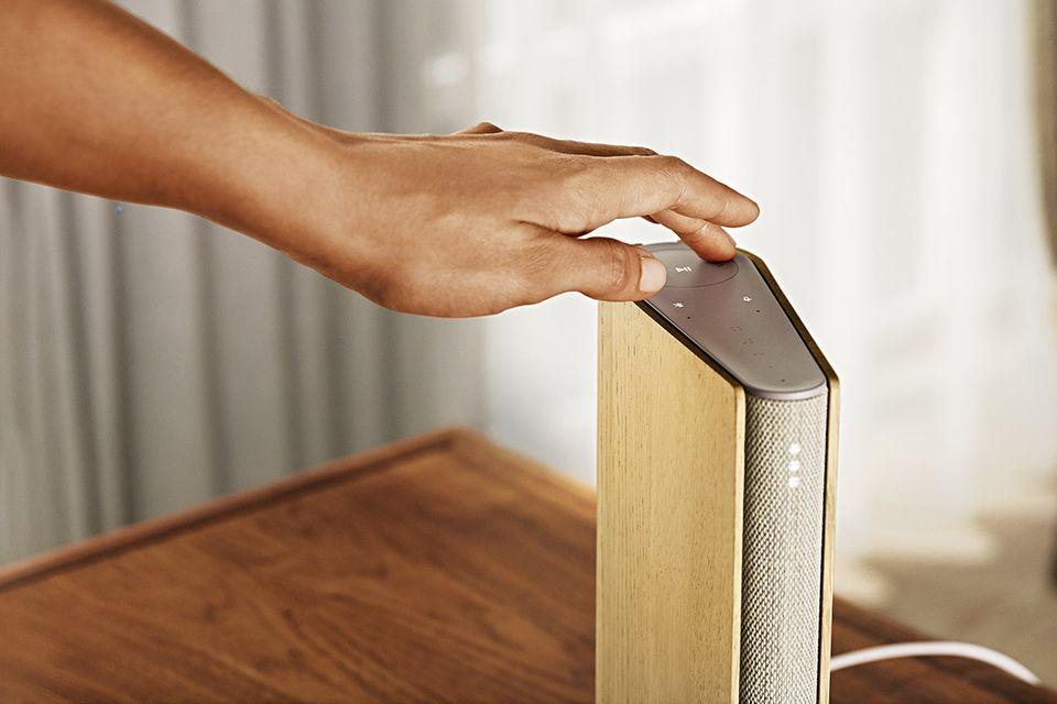 """Männliche Hand, die den Design-Lautsprecher """"Beosound Emerge"""" von Bang & Olufsen steuert"""