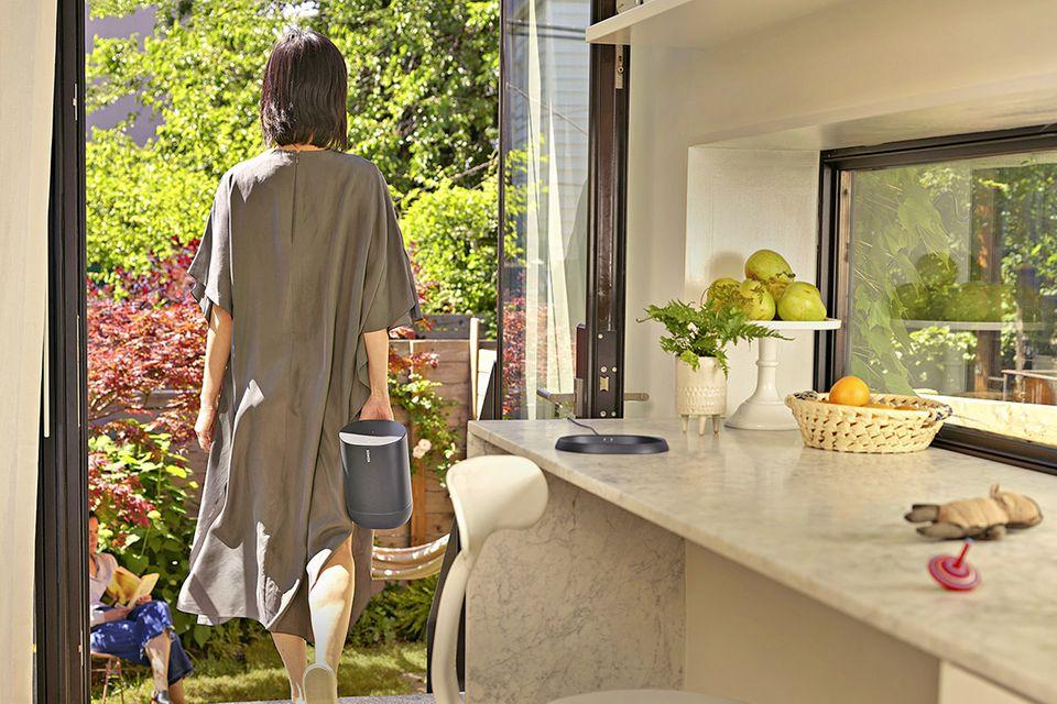 """Frau von hinten in einem grauen Kleid, die mit dem Lautsprecher """"Move"""" von Sonos in den Garten geht"""