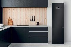Schwarze Küche mit Holz und Kühlschrank von Grundig