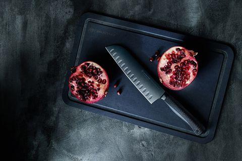 Schwarzes Küchenmesser auf einem schwarzen Schneidebrett mit einem geteilten Granatapfel