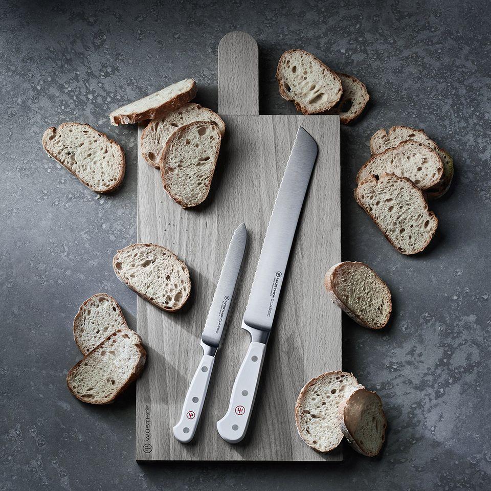Schneidebrett aus Holz, auf dem aufgeschnittenes Baguettebrot und zwei Brotmesser von Wüsthof liegen