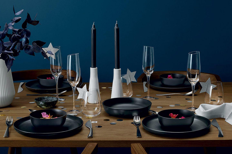 Festlich gedeckter Tisch für den Silvesterabend mit Geschirr, Sektgläsern, Kerzenhalter und Konfetti