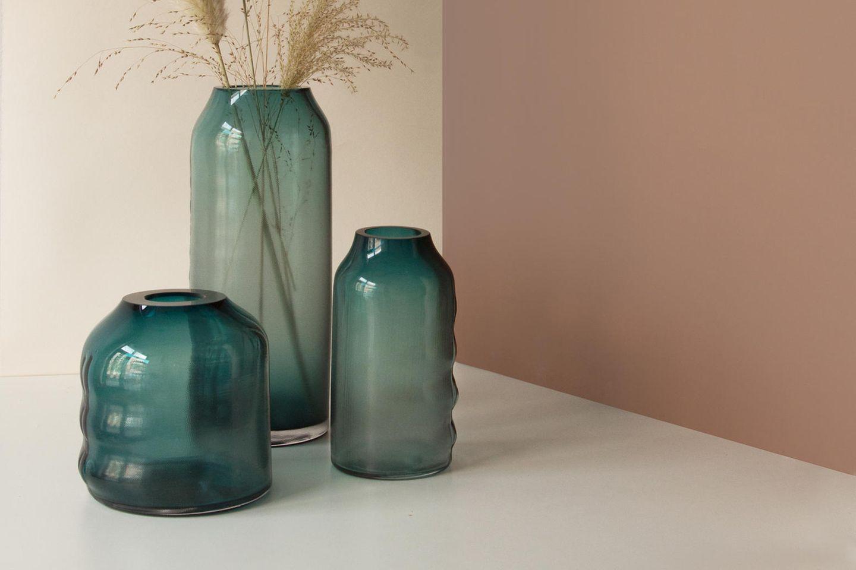 Grünfarbene Glasvasen mit Gräsern dekoriert