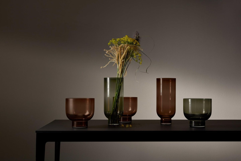Braune und grüne Glasvasen auf Holztisch dunkle Stimmung