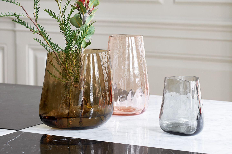 Verschieden farbige Glasvasen auf Marmortisch mit Blumendeko