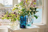 Blaue und durchsichtige Glasvasen mit Blumensträußen vor weißem Fensterrahmen