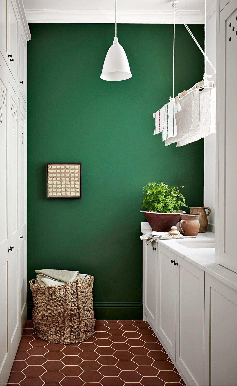 Weiße Küche mit hängendem Wäscheständer vor dunkelgrüner Wand
