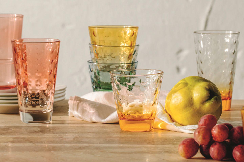 Verschiedenfarbige Trinkgläser vor weißem Hintergrund