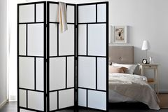 weißer Raumteiler aus Naturmaterialien vor einem Bett