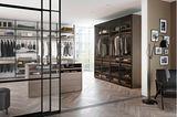 Schiebetüren aus Glas, die den begehbaren Kleiderschrank vom übrigen Raum abtrennen