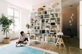 Großes weißes Bücheregal vor Holzwand in Wohnzimmer