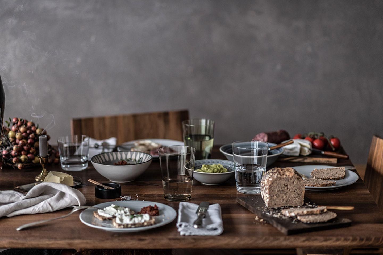 Gedeckter Tisch zum Abendbrot mit grauem Geschirr und verschiedenen Gläsern