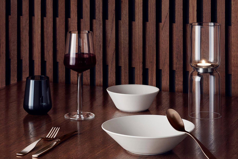 """Rotweinglas """"Essence"""" von Ittala auf einem Tisch mit zwei Schalen, Besteck, einem Wasserglas sowie einem Teelichthalter"""