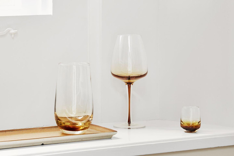 Ein Rotwein-, Wasser- sowie Schnapsglasvon BrosteCopenhagen mit dunkelgelbem Farbverlauf auf einer schmalen Fensterbank