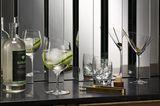 Ein Gin-, Martini- und ein Whiskyglas auf einer Theke vor einem Spiegel