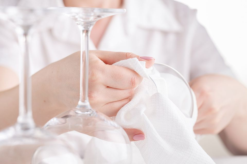 Frauenhände mit pinkem Nagellack polieren ein Weinglas